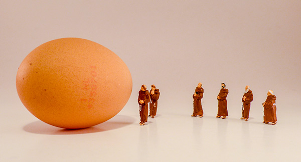 miniature monks admiring and egg